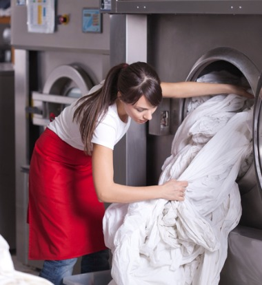 Woman Unloading Sheets from Commercial Laundry Equipment