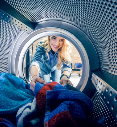 Woman Looking into Laundry Machine