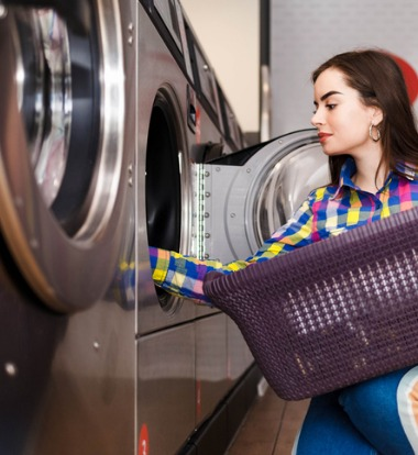 Woman taking clothes out of an Apartment Laundry Machine