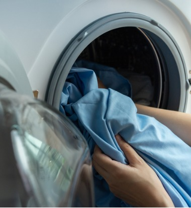 Woman Removing Laundry from Commercial Washers for Schools