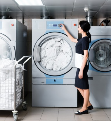 Woman Examining Laundry Machines for Hotels