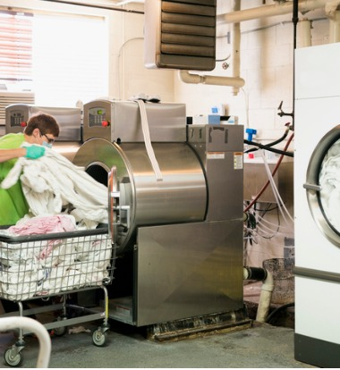 Woman Loading Commercial Washers for Healthcare