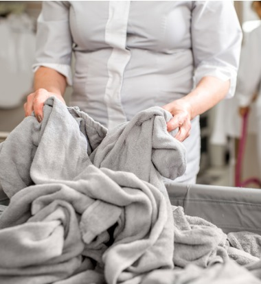 Woman Sorting Through Sheets for Commercial Laundry Equipment in Bloomington IL