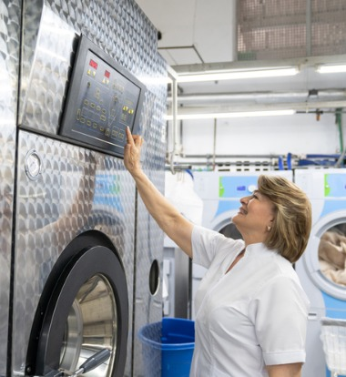 An employee programing Industrial Washing Machines in Burbank CA