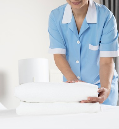 Woman Folding Laundry from Industrial Laundry Machines for Hotels